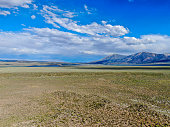 Long valley next the Lake Crowley, Mono County, California. USA. Green arid wetland with mountain range on the background during clouded summer.