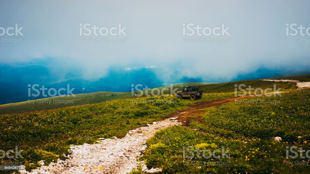 Aerial view of green hills. Summer landscape. Green grassy meadow on a hillside on top of mountain ridge with some forest under cloudy blue sky. Adygea, Lago-naki. stock photo