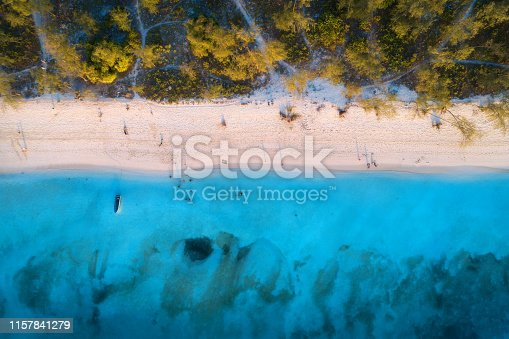 1136453253 istock photo Aerial view of green trees on the sandy beach and blue sea at sunset. Summer holiday. Indian Ocean in Zanzibar, Africa. Tropical landscape with palm trees, white sand, blue water, waves. Top view 1157841279