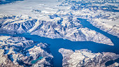 Aerial panoramic view of rugged Greenland scenery showing glaciers, icebergs and mountain ridges on a beautiful sunny day with blue sky and clouds