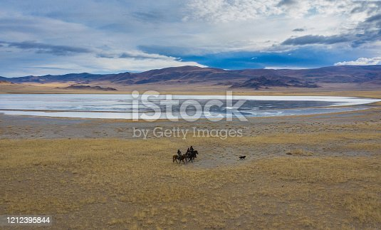 Aerial view of group of eagle hunters near the river in Mongolia