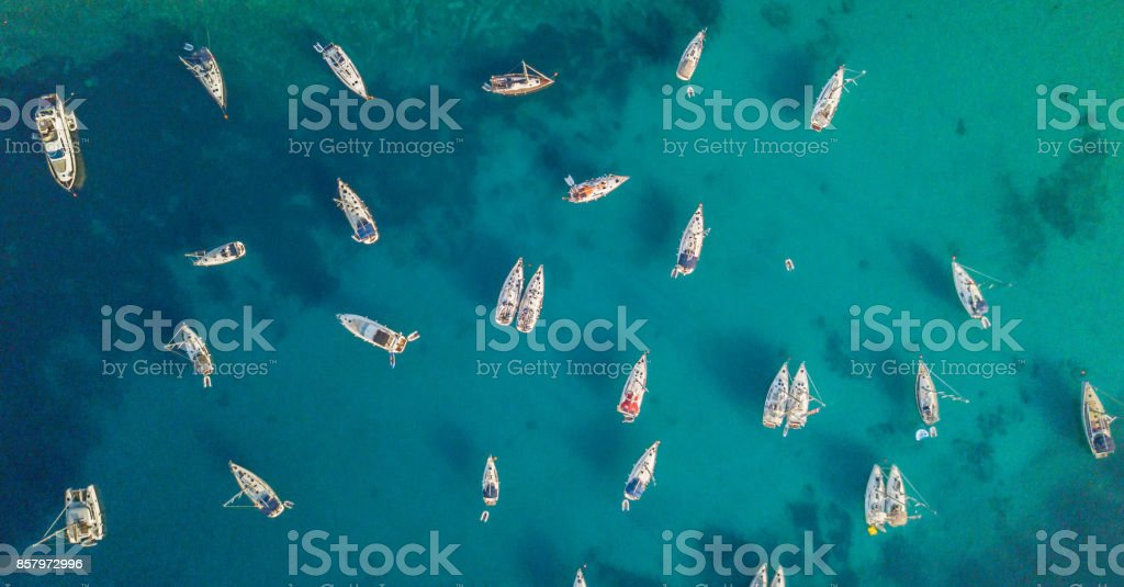 Aerial view of group of sailing boats anchoring on buoys. стоковое фото