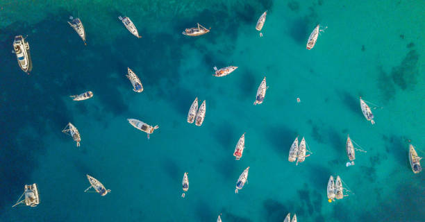 Aerial view of group of sailing boats anchoring on buoys. stock photo