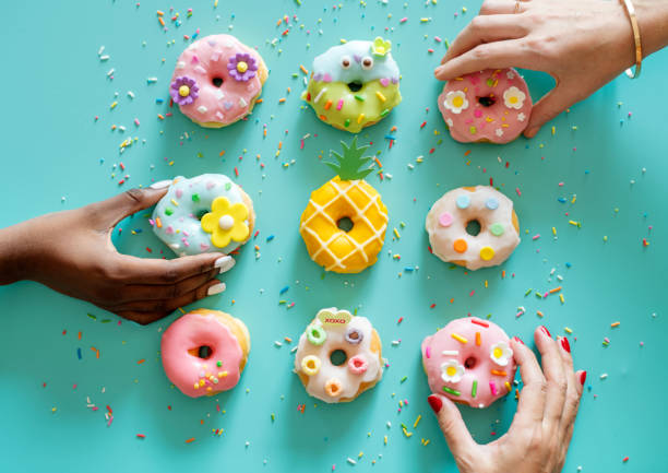 Aerial view of hands getting donut stock photo
