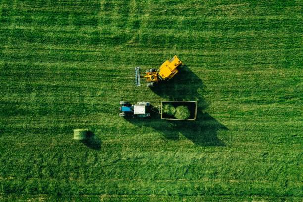 Luftaufnahme des Erntefeldes mit Traktor bewegt Heuballen – Foto