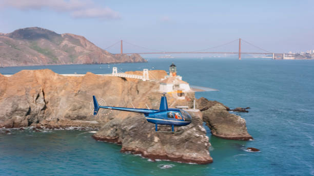 Aerial view of Helicopter flying past the Point Bonita Lighthouse at the San Francisco Bay entrance Aerial view of a helicopter flying past the Point Bonita Lighthouse at the entrance into the San Francisco Bay on a sunny day, California, USA. san francisco bay stock pictures, royalty-free photos & images