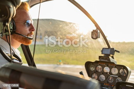 Portrait of redhead helicopter pilot sitting in cockpit, wearing sunglasses and headset