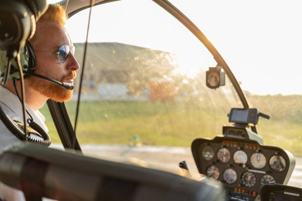 Aerial view of helicopter pilot welcoming passengers Portrait of redhead helicopter pilot sitting in cockpit, wearing sunglasses and headset pilot stock pictures, royalty-free photos & images