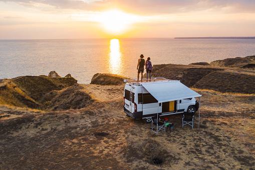 Aerial view of the heterosexual couple on the roof of camper van on seaside  at sunset