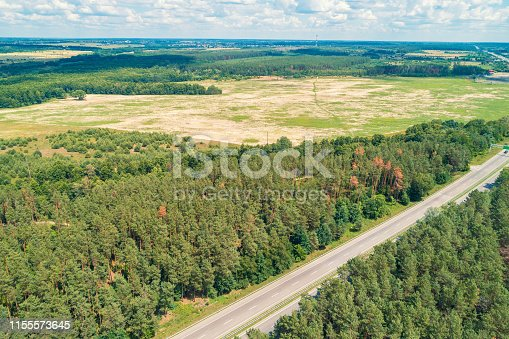 istock Aerial view of highway, countryside, wood, and fields 1155573645