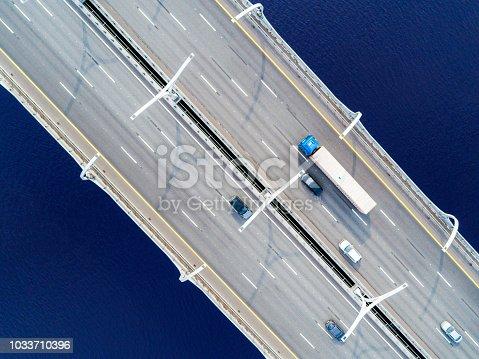 Aerial view of highway in the ocean. Cars crossing bridge interchange overpass. Highway interchange with traffic. Aerial bird's eye highway. Expressway. Road junction. Car passing. Bridge with traffic