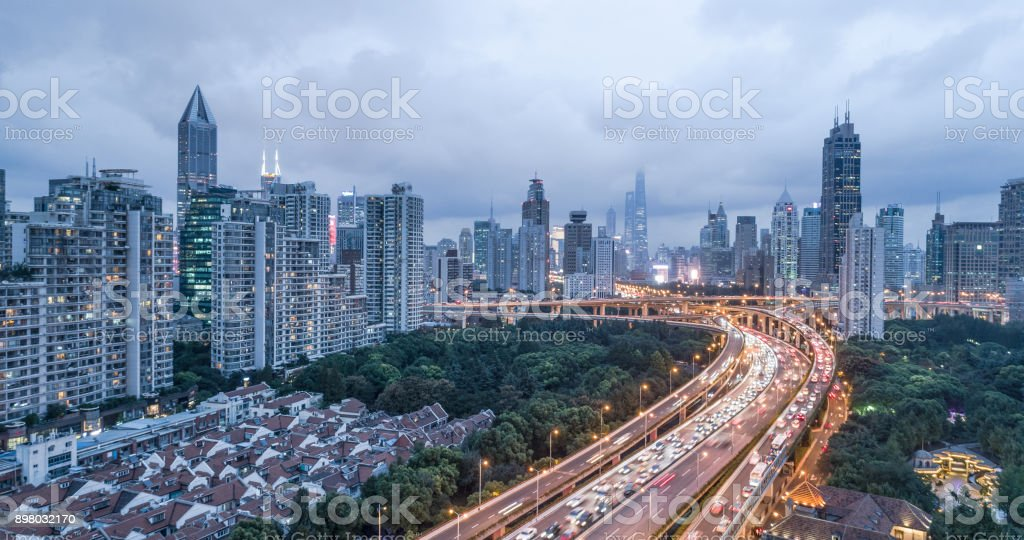 aerial view of highway interchange and buildings of shanghai city in the evening of a cloudy day stock photo