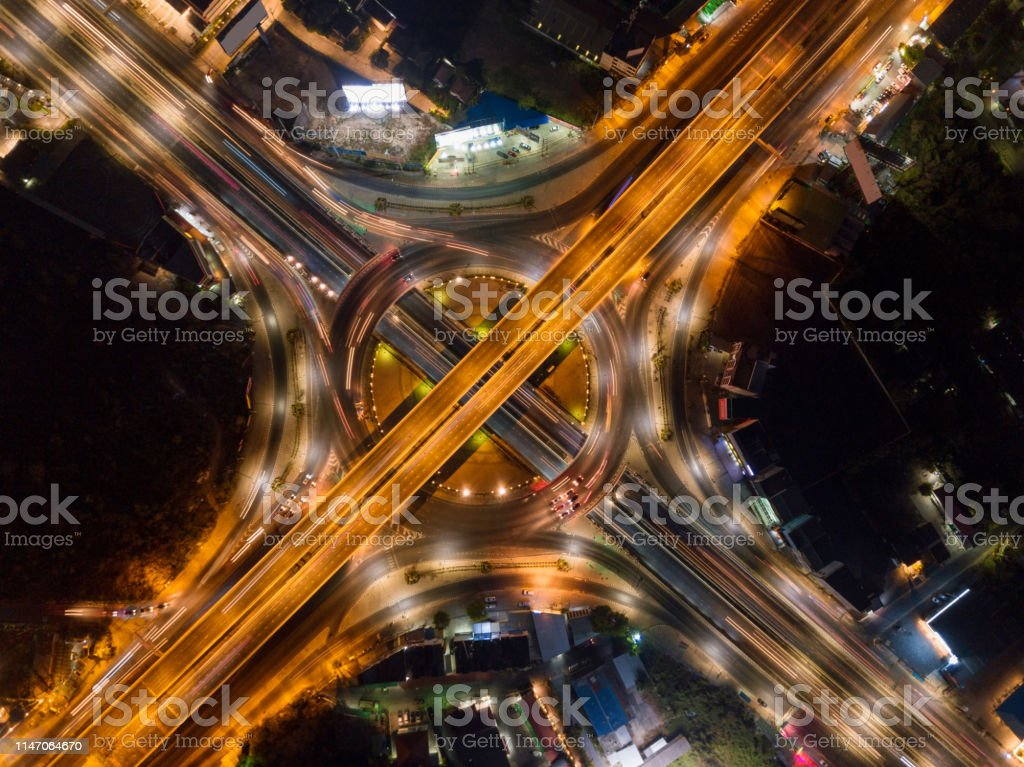 Aerial View Of Highway Junctions With Roundabout Bridge