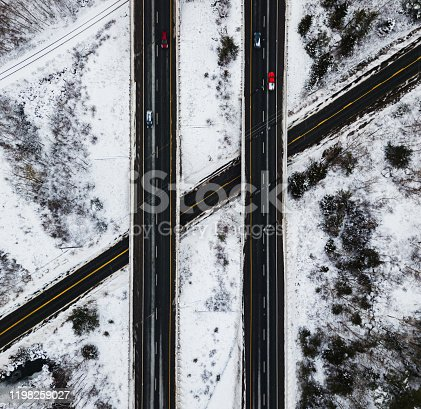 Aerial drone view of a multi-lane highway & overpass in Winter.