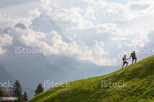 Photo of Aerial view of hiking couple traversing alpine meadow in the morning