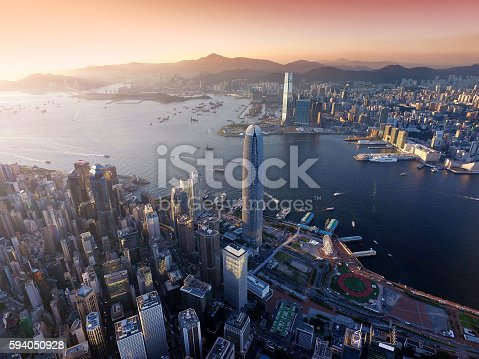 Dramatic skyline of Hong Kong Island and busy ships navigates across the Victoria Harbour during beautiful sunset on a non air-polluted day.