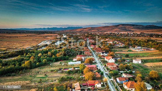 High angle drone shot depicting the architecture - the small cottages and houses - of a traditional village in Transylvania, Romania. A road cuts directly through the image and we can see people's gardens, which they mainly use for growing vegetables. Room for copy space.