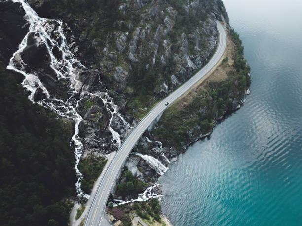 vista aérea de la gran cascada de agua cayendo en el lago turquesa y carretera en noruega - noruega fotografías e imágenes de stock