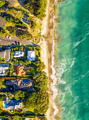 A view of beachside homes in the Takapuna district of Auckland, New Zealand from directly above the beach.