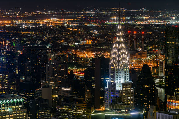 aerial view of illuminated buildings in manhattan - chrysler building stock photos and pictures