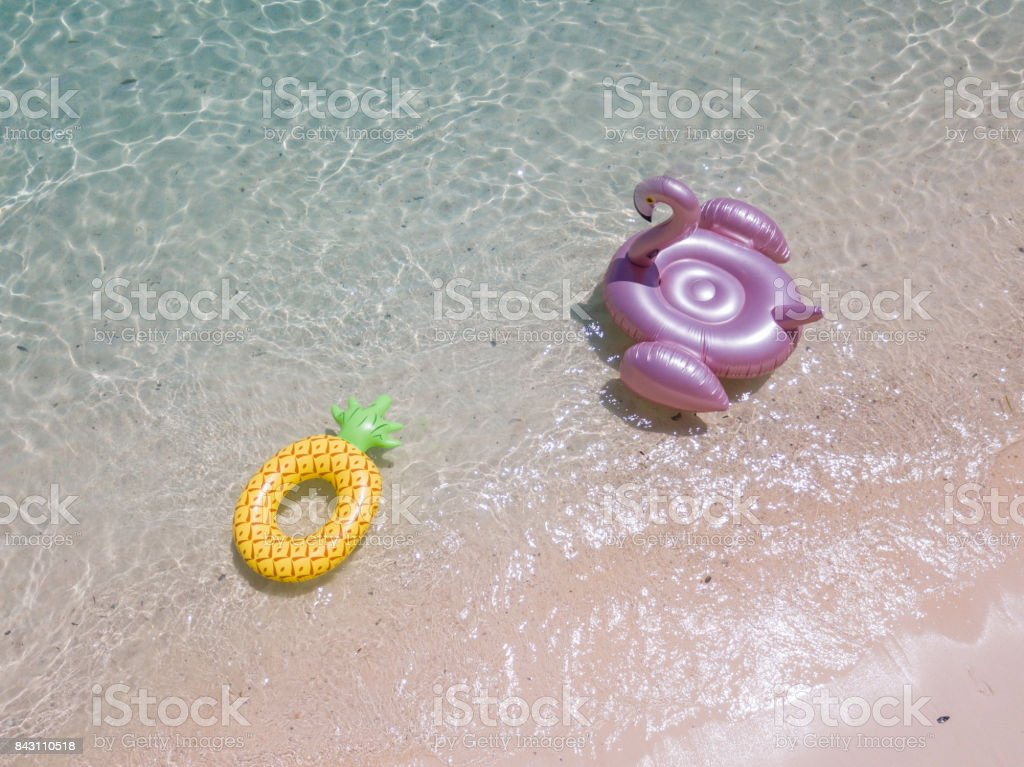 Aerial view of inflatable giant pink flamingo and pineapple float on the sea stock photo