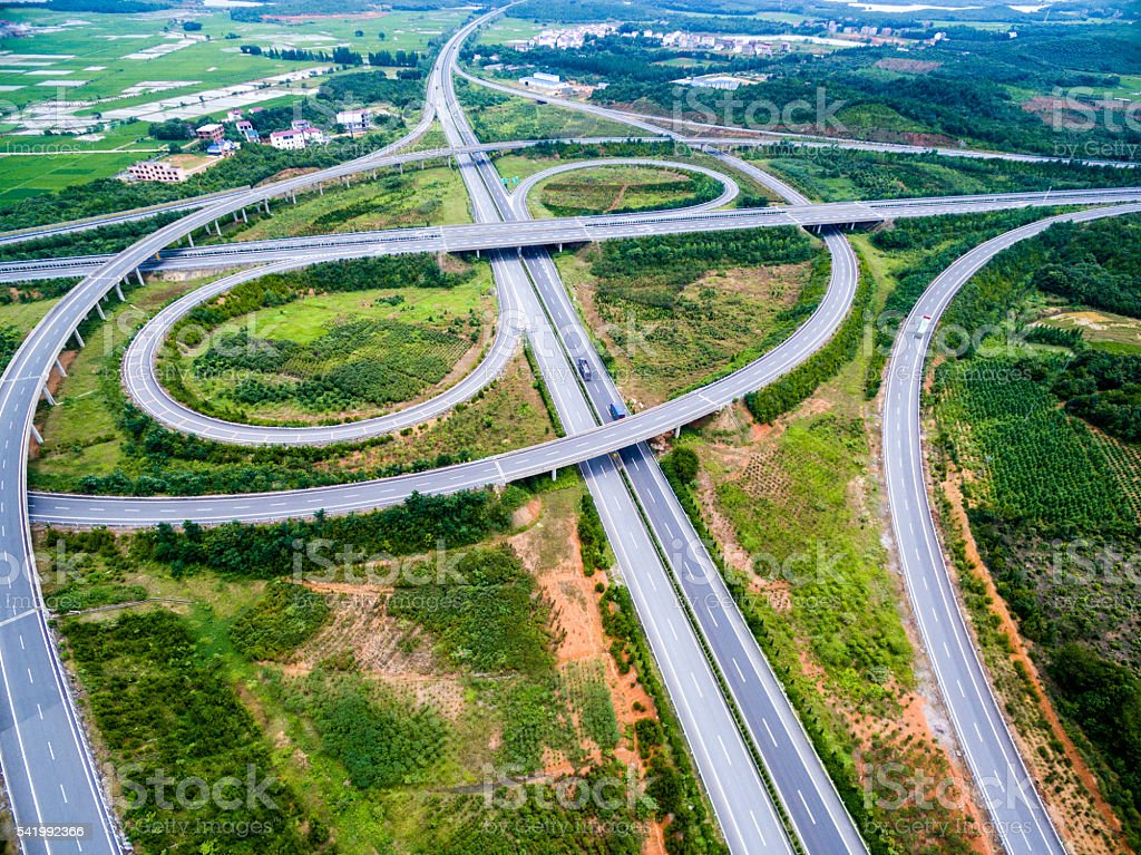 Aerial view of intersecting highways near trees stock photo
