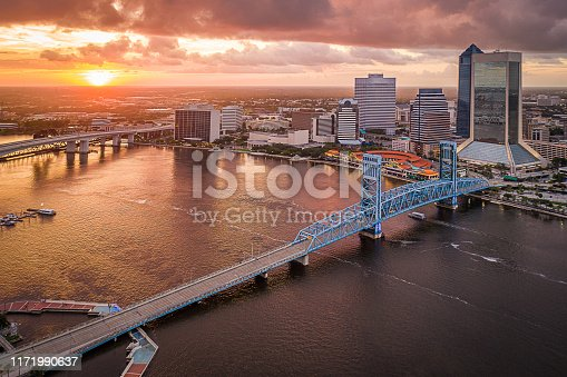 Jacksonville, Florida is bathed in the day's final rays of sunlight in this aerial view of the St. Johns River and downtown skyline.