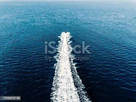Aerial view of jet skier in blue sea. Jet ski in turquoise clear water racing in high speed.