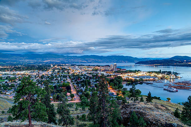 aerial view of kelowna skyline at night - british columbia stock pictures, royalty-free photos & images