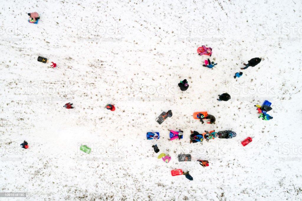 Luftaufnahme von Kindern und Eltern Rodeln auf Wintertag – Foto