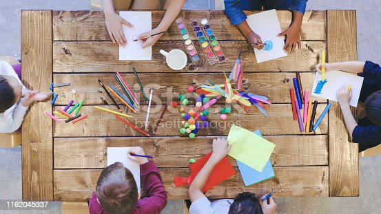 Aerial overhead view of a multi-ethnic group of elementary age children doing arts and crafts. The kids are seated around a large table that is covered by coloring and painting supplies. The creative kids are having fun and sharing.