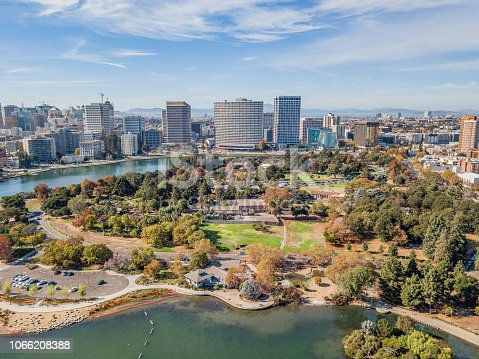 Aerial view of Lake Merritt and downtown Oakland on a sunny day. Skyscrapers fill the horizon with a bright blue sky. Downtown district fills the waterfront.