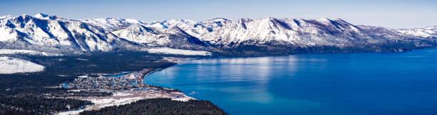 luftaufnahme des lake tahoe an einem sonnigen wintertag, sierra berge schneebedeckt im hintergrund, california - lake tahoe winter stock-fotos und bilder