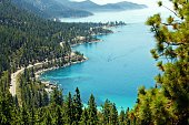 The view from a mountain above Lake Tahoe with a view of a boat and the road