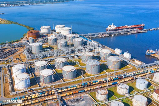Aerial view of large fuel storage tanks at oil refinery industrial zone in the cargo seaport, and ship tanker at unloading