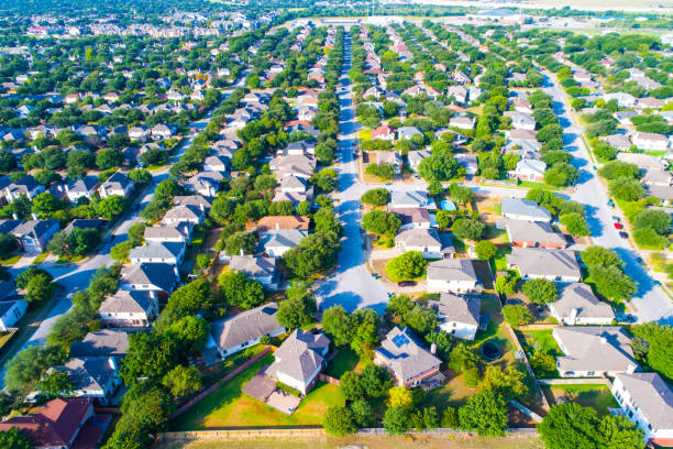 aerial view of large suburb entire view repeated homes and perfect rows of houses and rooftops looking down on neighborhood in north austin near wells branch - urban sprawl stock photos and pictures