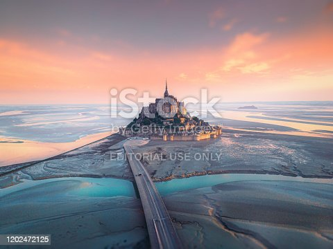 Aerial view of famous Mont Saint Michel tidal island and jetty bridge at a beautiful  sunrise time in Normandy, Northern France