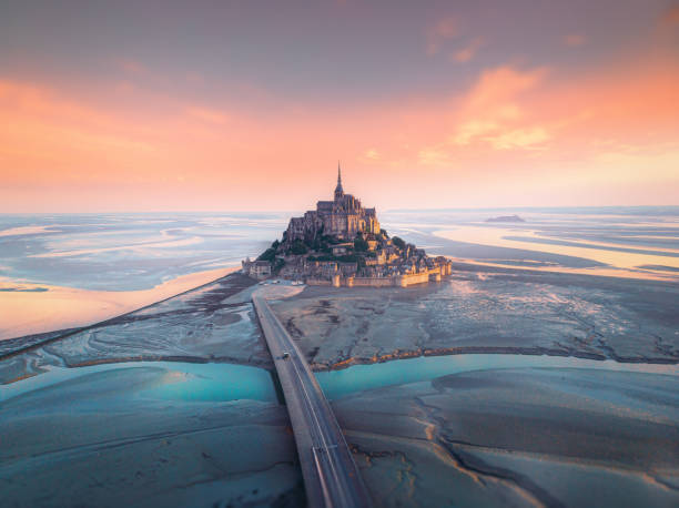 Aerial view of Le Mont Saint-Michel in France Aerial view of famous Mont Saint Michel tidal island and jetty bridge at a beautiful  sunrise time in Normandy, Northern France manche stock pictures, royalty-free photos & images