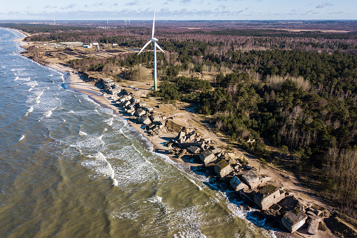 Aerial view of Liepaja Northern Forts, old abandoned fortifications at Baltic sea coast in Latvia and wind turbine