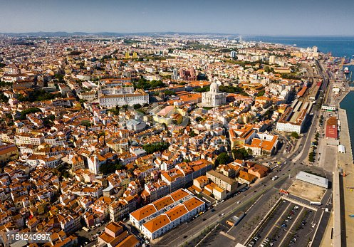 Picturesque aerial view of historical district of Lisbon on bank of Tagus river with medieval Monastery and white baroque building of Church of Santa Engracia, Portugal