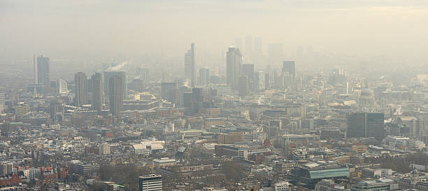 Aerial View of London in the Fog Aerial view of London's financial district in the fog. smog stock pictures, royalty-free photos & images