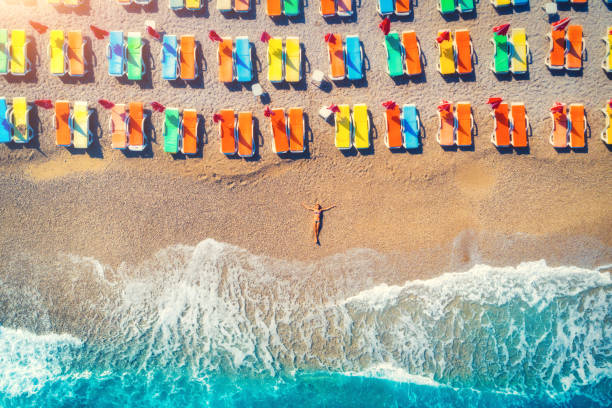 Aerial view of lying woman on the beach with colorful chaise-lounges. Young woman on the sea at sunset in Oludeniz, Turkey. Top view. Seascape with girl on the seashore, azure water and waves. Holiday stock photo