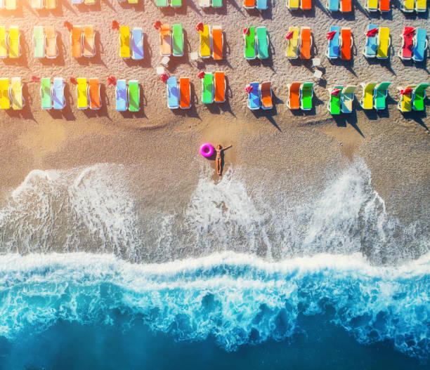 luftaufnahme des lügens frau mit schwimmring im meer in ölüdeniz, türkei. sommer seestück mit mädchen, blauen wasser, wellen und sandigen strand mit bunten liegesessel bei sonnenuntergang. draufsicht von drohne - sessel türkis stock-fotos und bilder