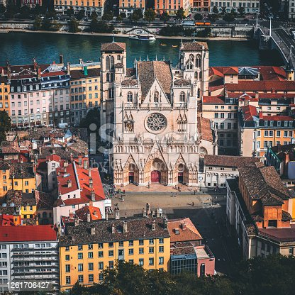 Aerial view of Lyon cityscape with St Jean Cathedral monument in foreground along Saone riverbank and red rooftops from large Place Bellecour famous town square. Photo taken in Lyon city, Unesco World Heritage Site, in Rhone department, Auvergne-Rhone-Alpes region in France, Europe during a sunny summer day.