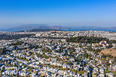 An aerial view over the city of San Francisco on a sunny day. Majestic view as we look over the city with parks, row houses , iconic buildings and the Golden Gate Bridge in the distance. The entire city is in view.