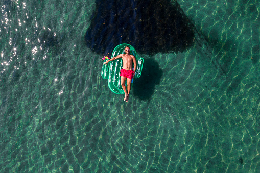 Drone view of one man relaxing on inflatable mattress