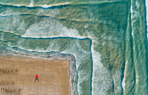 Aerial view of man lying on beach. Aerial view of man lying on beach. wellington new zealand stock pictures, royalty-free photos & images