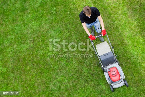 An overhead view of a man mowing a green lawn.  The man is wearing a black T-shirt, blue jeans and gray boots.  He is wearing a pair of red gloves.  The lawn mower is red and light gray with a part that is dark gray.