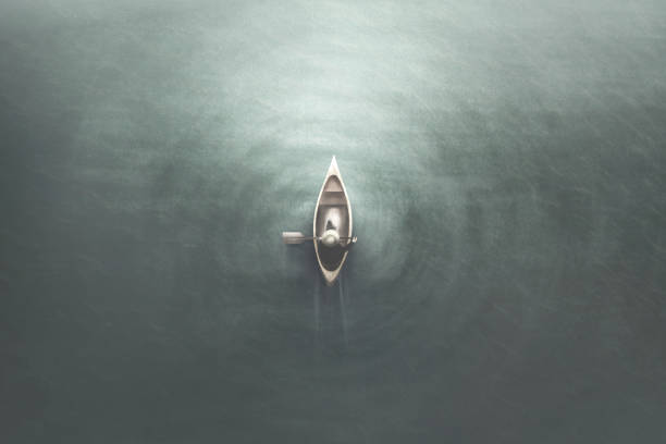 aerial view of man paddling on a canoe in the water, minimal summer sport concept stock photo
