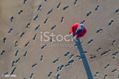 istock Aerial view of man piloting a drone on tropical beach 1199515592